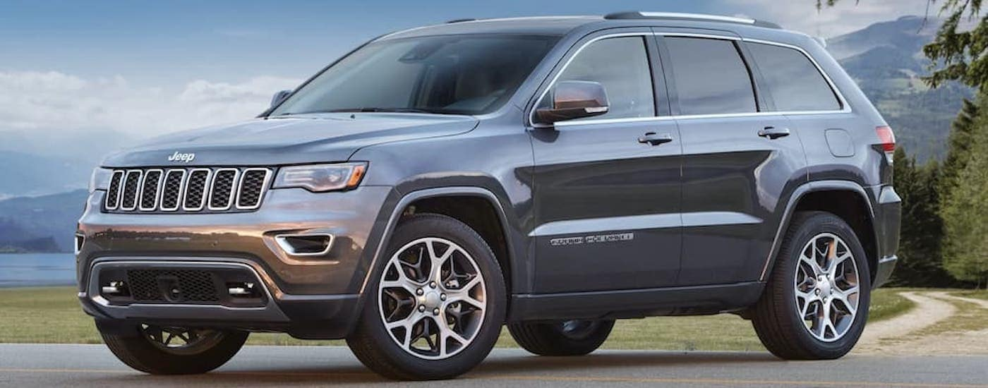 A grey 2018 Used Jeep Grand Cherokee is parked in front of a lake and mountain.
