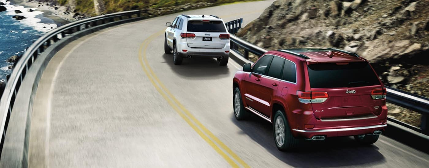 A red 2020 Used Jeep Grand Cherokee is following a white one around a corner on a road next to the ocean.