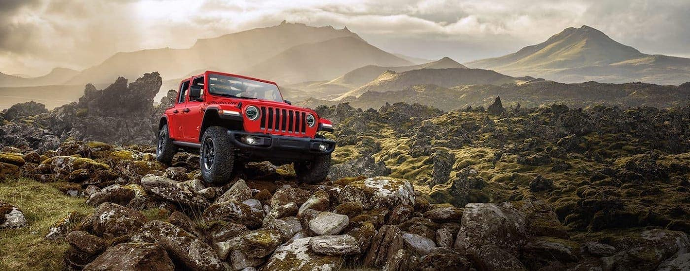 A red 2021 Jeep Wrangler Unlimited is shown climbing over rocks in front of distant mountains.