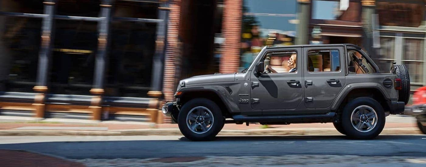 A gray 2021 Jeep Wrangler Unlimited with the roof off is shown from the side driving on a city street.