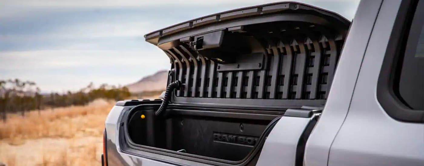 A closeup shows the open Rambox storage on a silver 2021 Ram 1500.