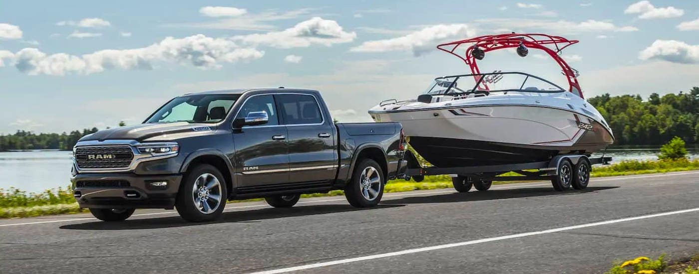 A gray 2021 Ram 1500 is towing a boat on an empty highway.