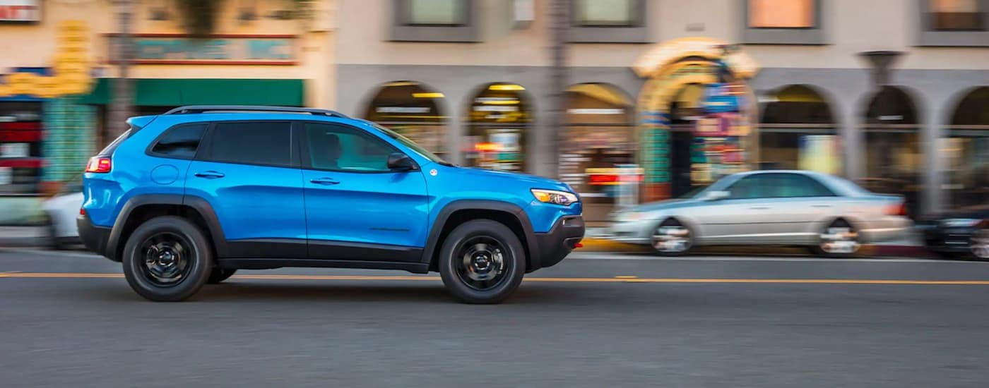 A blue 2020 Jeep Cherokee is driving on a city street after leaving a used Jeep dealer near me.