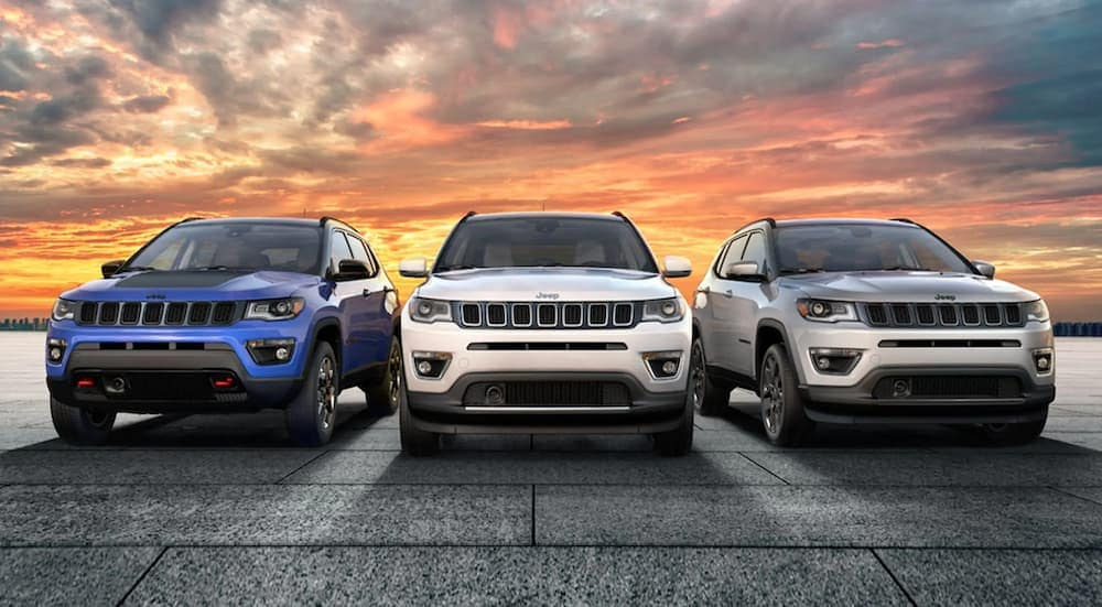 A blue, a white, and a silver 2020 Jeep Compass are parked in front of a sunset.