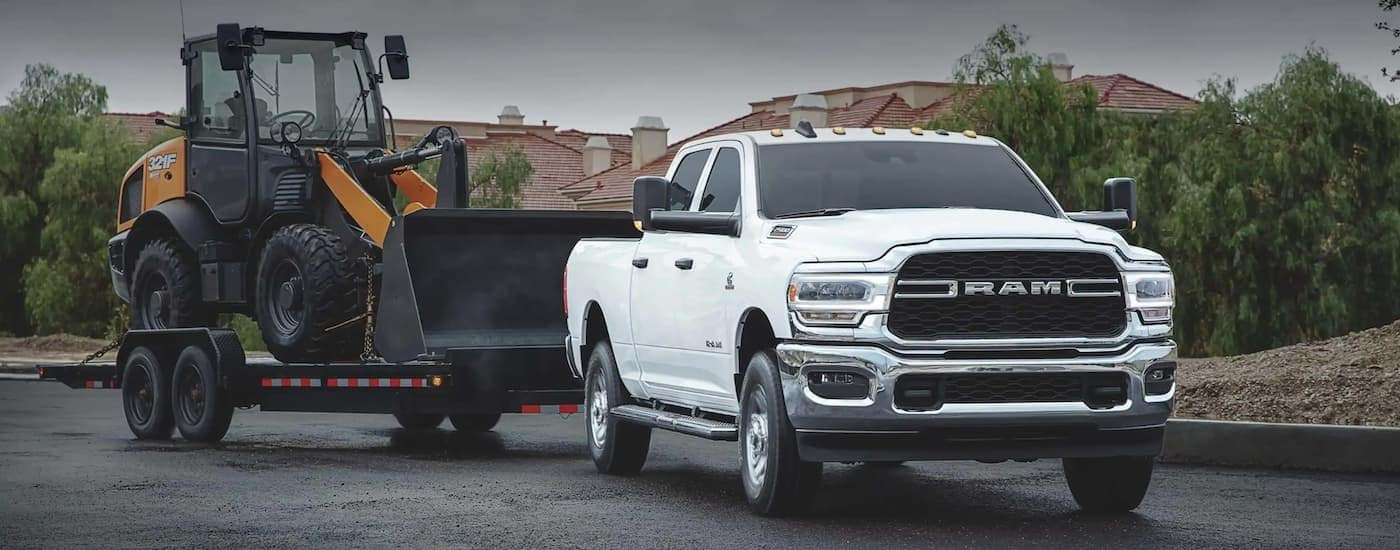 A white 2020 used Ram 2500 is towing a loader in a neighborhood.
