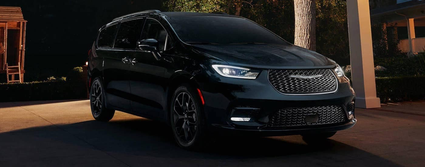 A black 2021 Chrysler Pacifica Hybrid is shown at night, angled right.