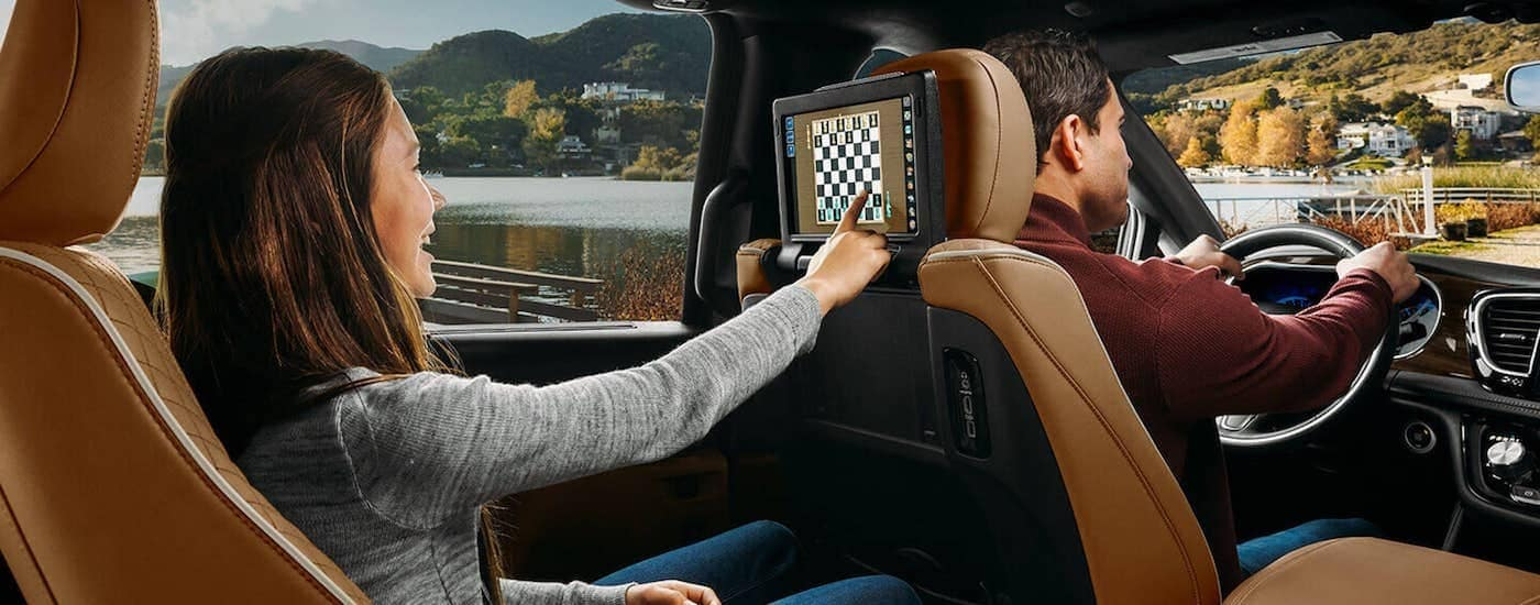 A close up is shown of a girl playing chess on the seat back touchscreen of a 2021 Chrysler Pacifica.