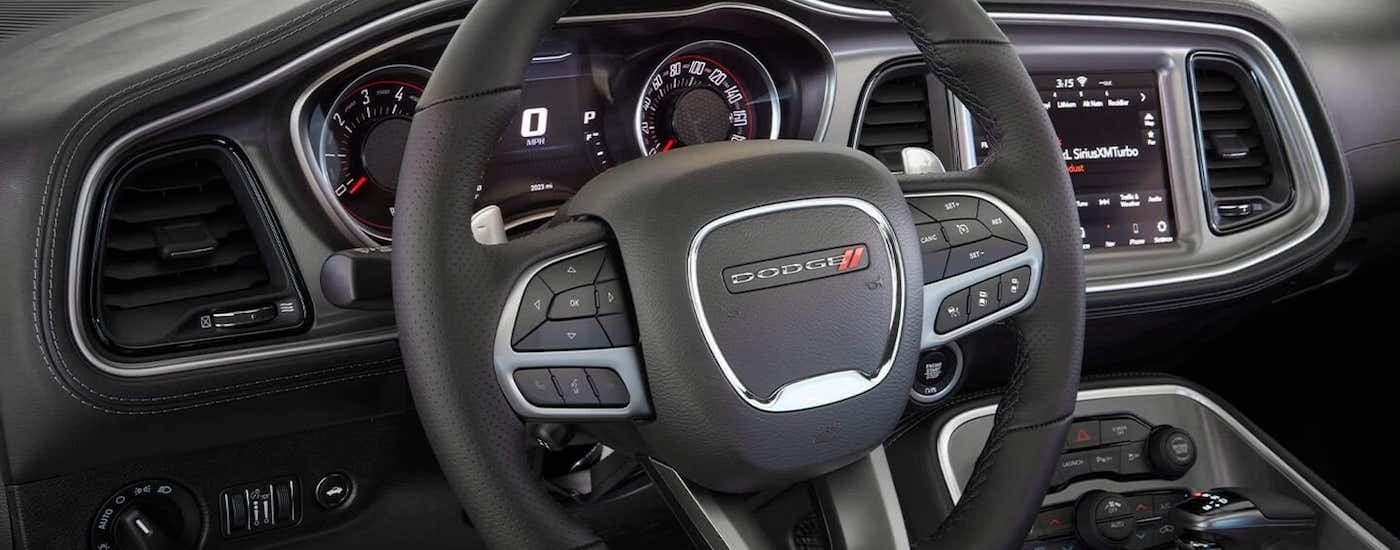 A close up is shown of the steering wheel and infotainment screen is shown on a 2021 Dodge Challenger.