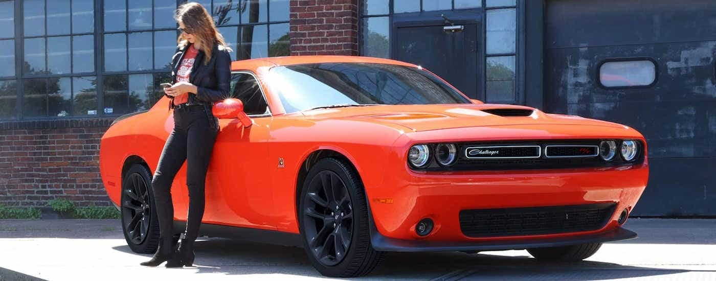 An orange and black 2021 Dodge Challenger R\T Scat Pack is parked with a brick building in the background and a woman leaning against it.