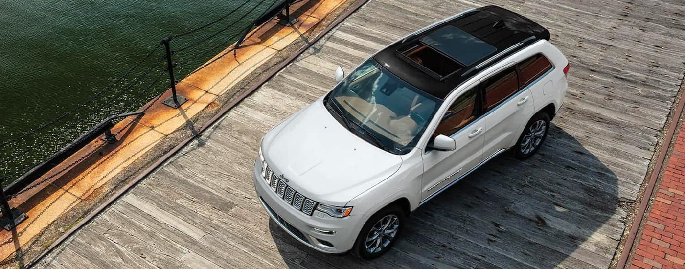 A white 2021 Jeep Grand Cherokee is shown from a high angle parked on a dock.