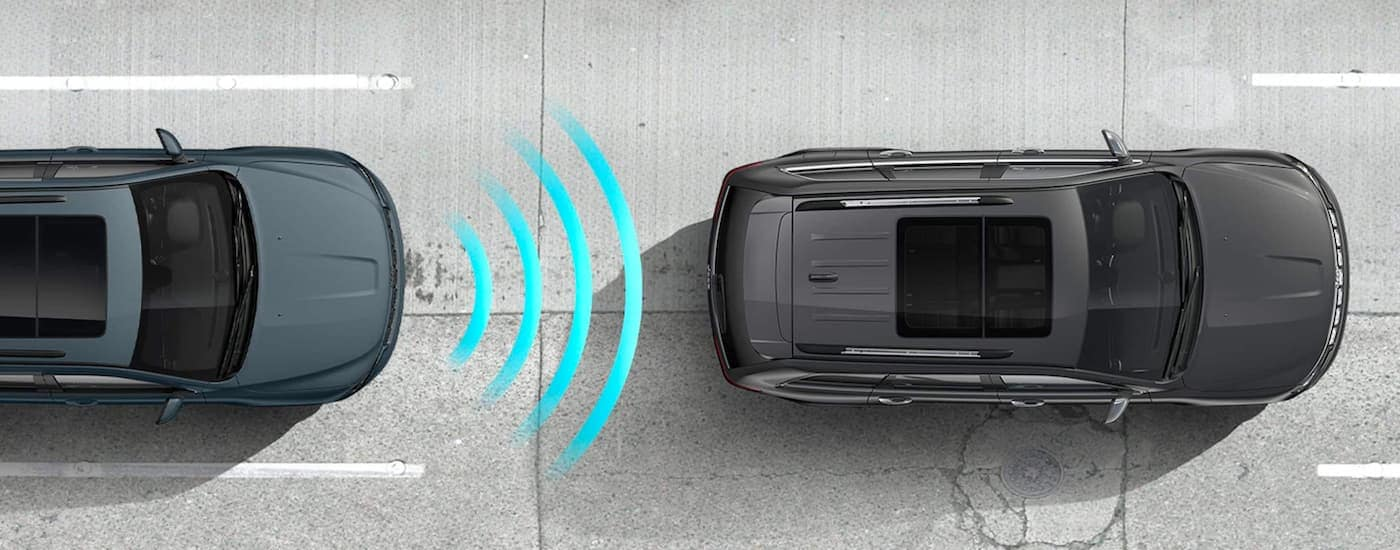 A blue and a grey 2021 Jeep Grand Cherokee are shown from an aerial view with collision warning icon.
