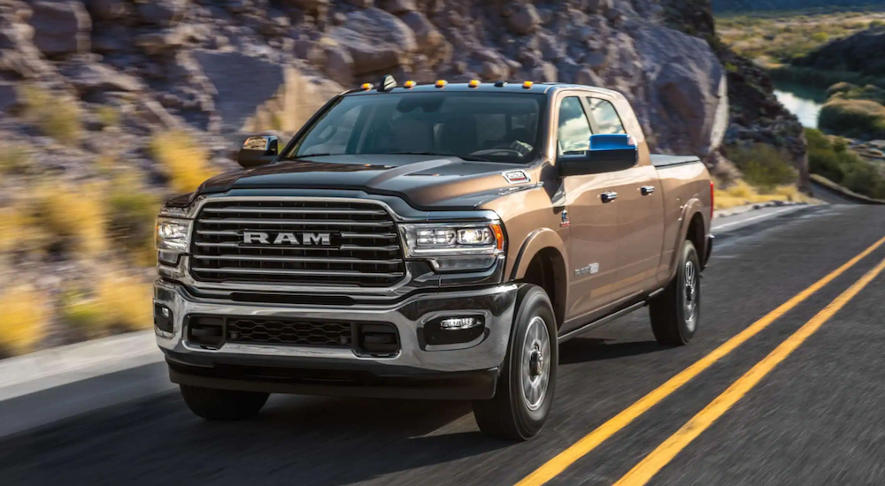 A brown 2020 used Ram 2500 is driving past a rocky hill.
