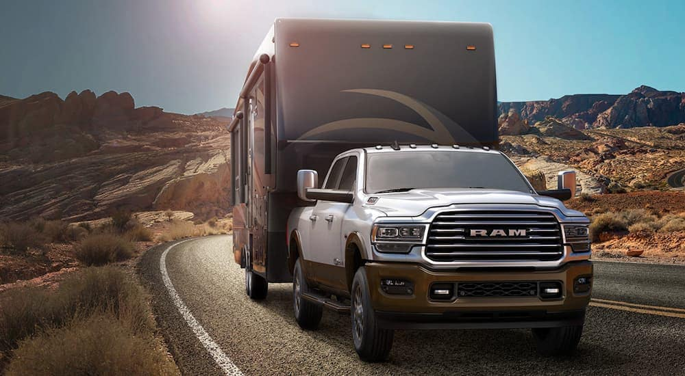 A white 2020 used Ram 2500 is towing a fifth-wheel camper on a desert road.
