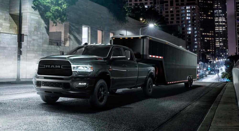 A black 2021 Ram 2500 is towing a black trailer in a city at night.
