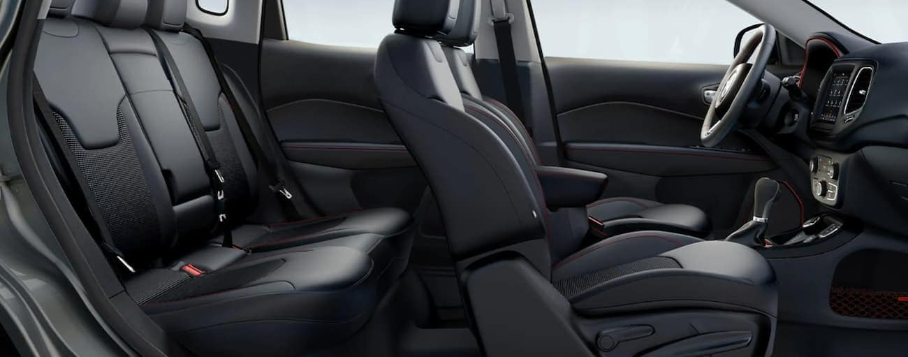 The black interior of a 2021 Jeep Compass is shown from the side.