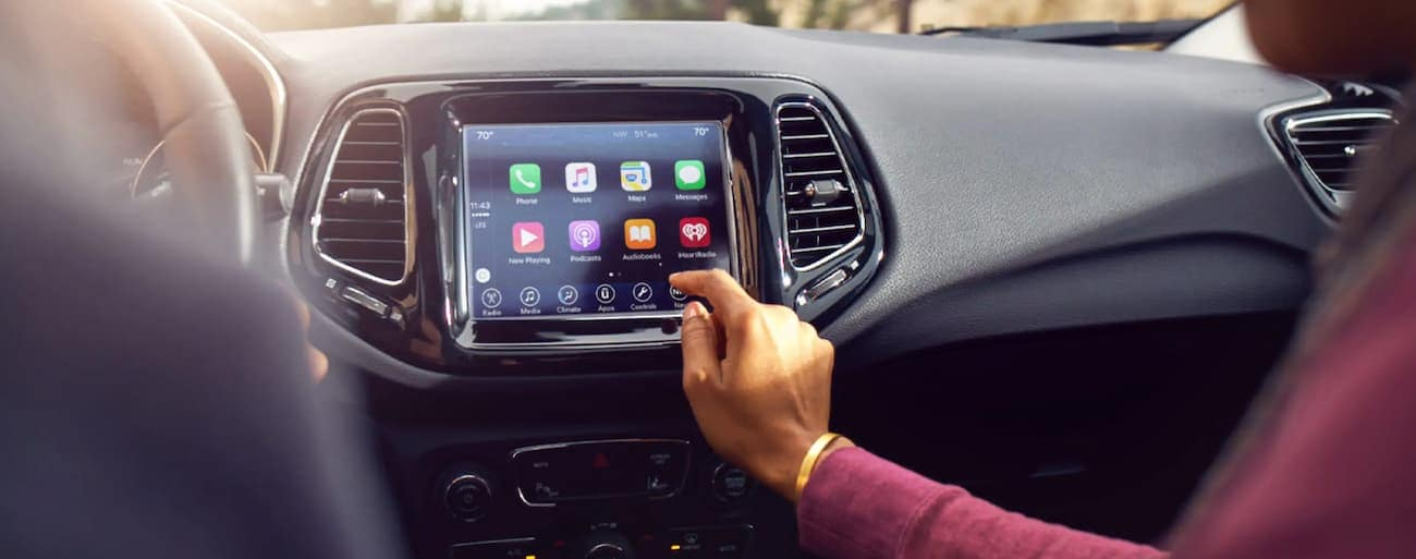 A passenger in a 2021 Jeep Compass is using the touch screen.
