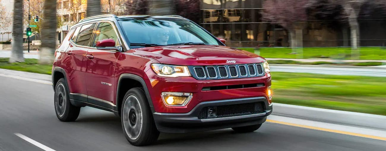 A red 2021 Jeep Compass is driving on a multi-lane road past grass.