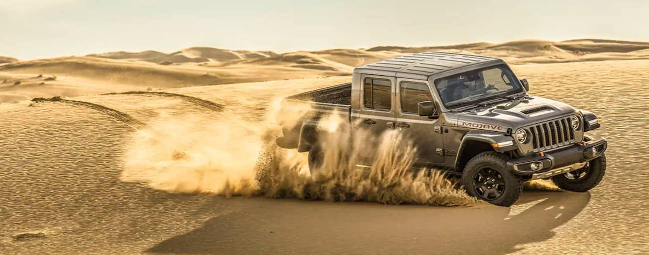 A grey 2021 Jeep Gladiator Mojave is off-roading in desert sand.