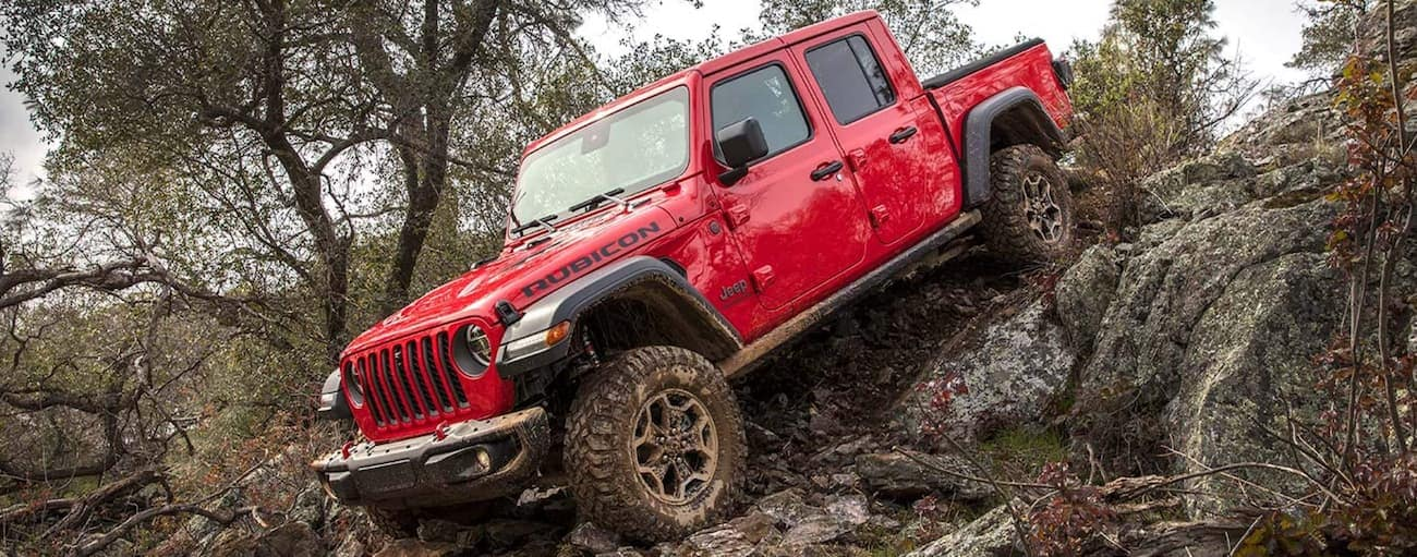 A red 2021 Jeep Gladiator Rubicon is off-roading on a rocky trail.