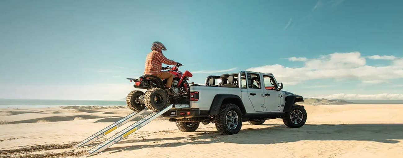 A person is riding a four-wheeler up ramps into the bed of a silver 2021 Jeep Gladiator while parked on beach sand.