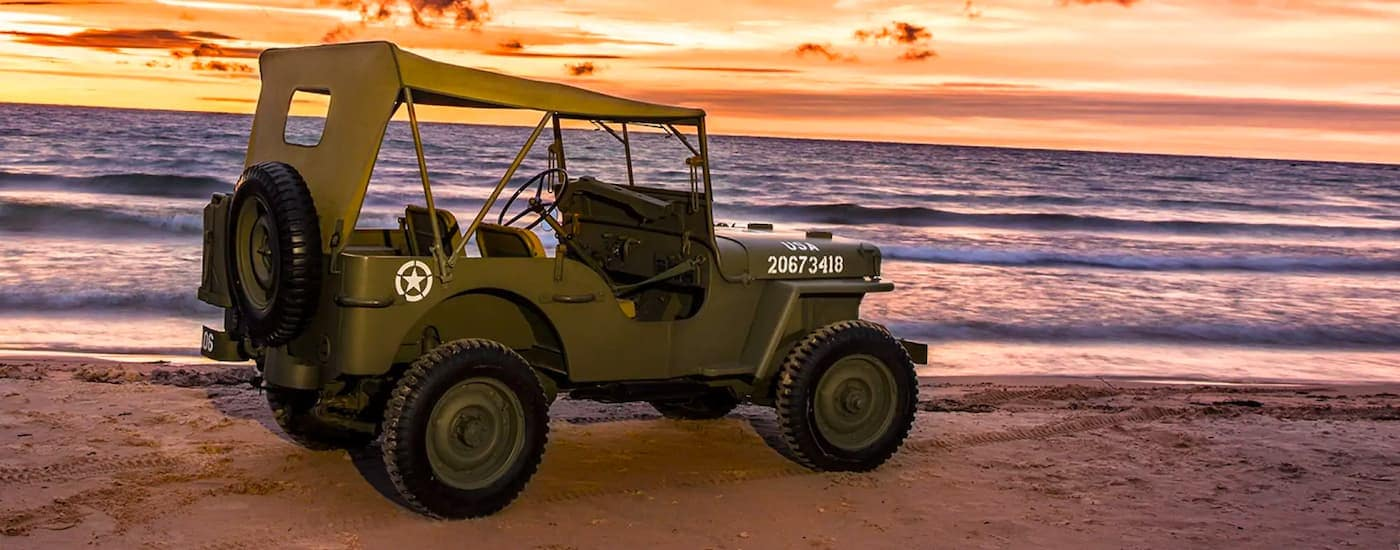 An olive green 1942 Jeep Wrangler Willys is shown from the side while parked on the beach with an orange sunset in the background.