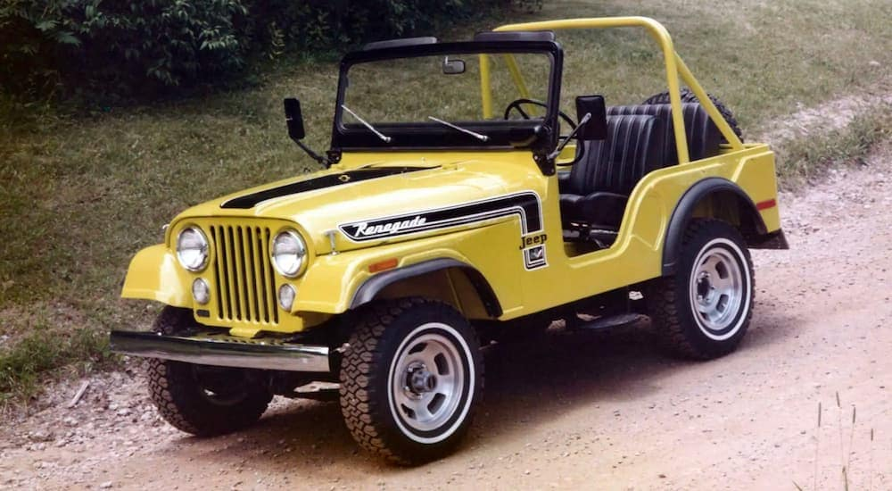 A yellow 1973 Jeep Wrangler CJ-5 Renegade is parked on a dirt path with no top or doors.