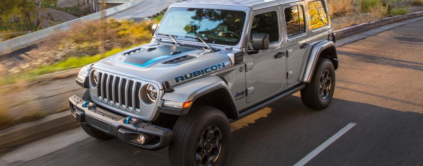 A silver 20221 Jeep Wrangler 4xe is driving on a city street.