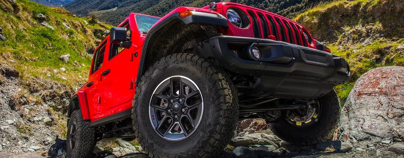 A red 2021 Jeep Wrangler is shown from a low angle parked on rocks.
