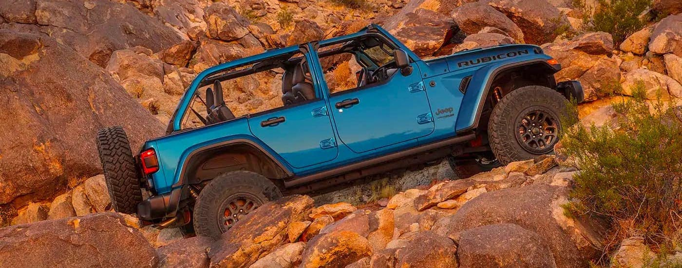 A blue 2021 Jeep Wrangler Rubicon 392 with no roof is shown from the side  climbing up a rocky hill.