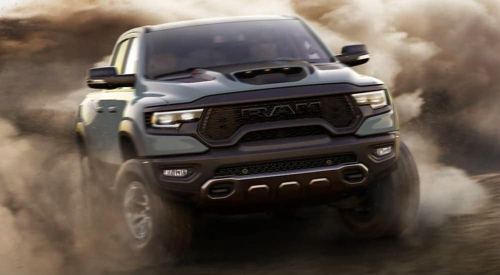 A green 2021 Ram 1500 TRX from a Ram TRX dealer is kicking up sand while off-roading.