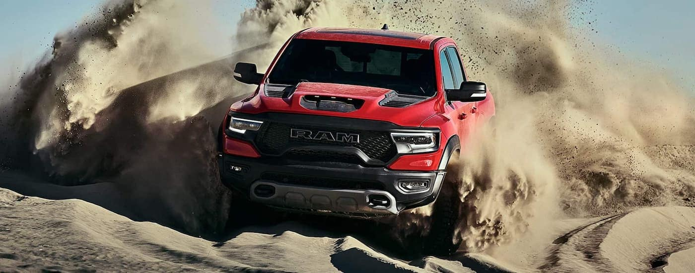 A red 2021 Ram 1500 TRX is kicking up sand while off-roading on dunes.