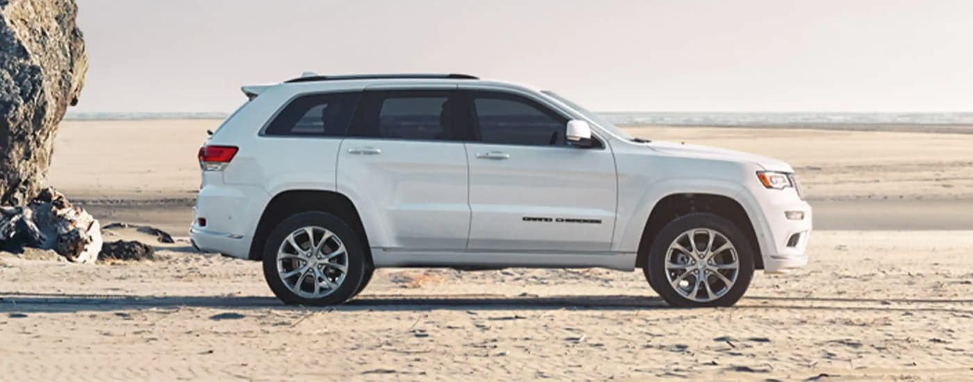 A white 2020 Jeep Grand Cherokee is shown from the side on a beach.