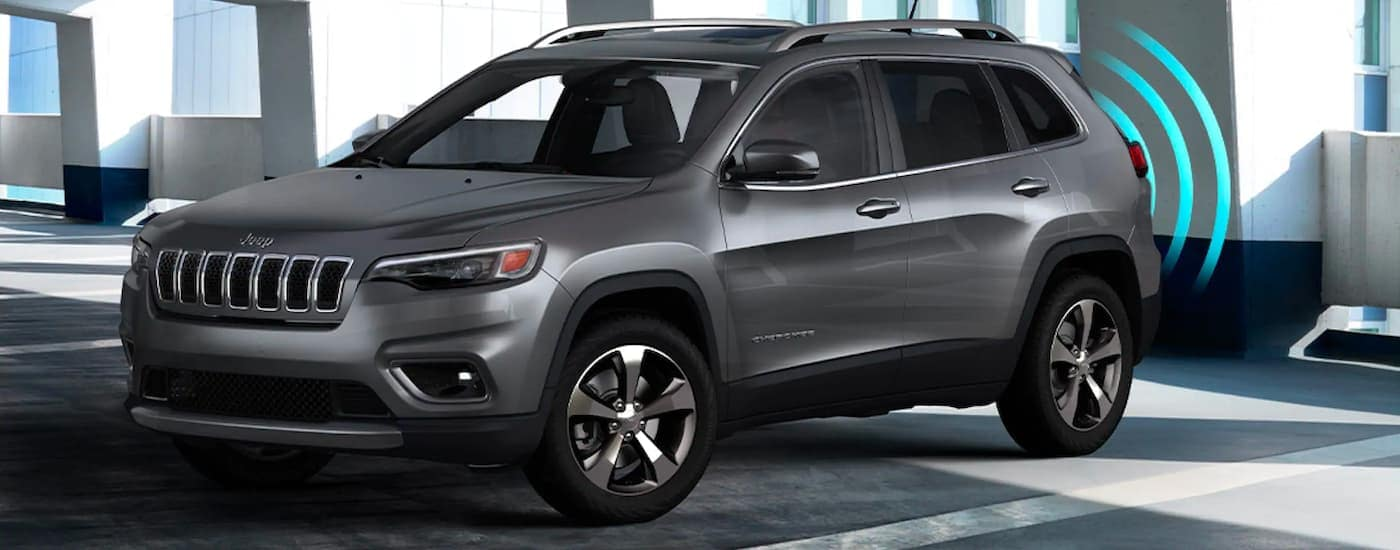 A dark gray 2021 Jeep Cherokee is shown from the side with park assist sensor lines coming from behind the vehicle.