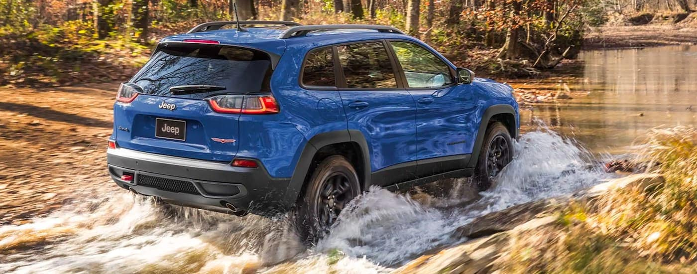 A blue 2021 Jeep Cherokee is shown from behind driving through a river.
