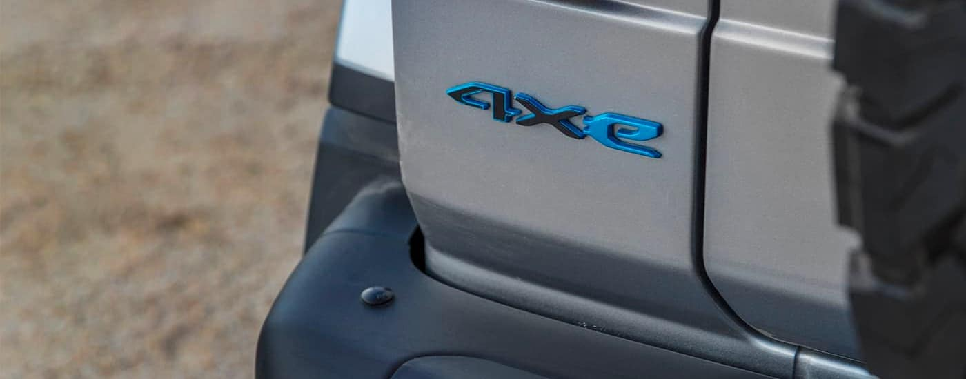 A close up shows the blue 4xe emblem on a gray 2021 Jeep Wrangler 4xe.
