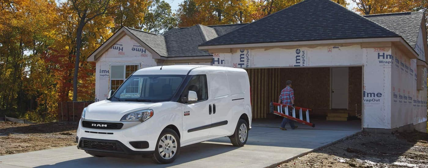A white 2021 Promaster City is parked in front of an unfinished home and a worker carrying a ladder.