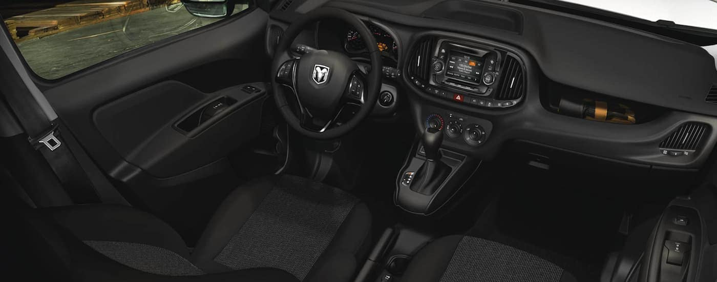 The black front seats and dashboard are shown in a 2021 Ram Promaster City.