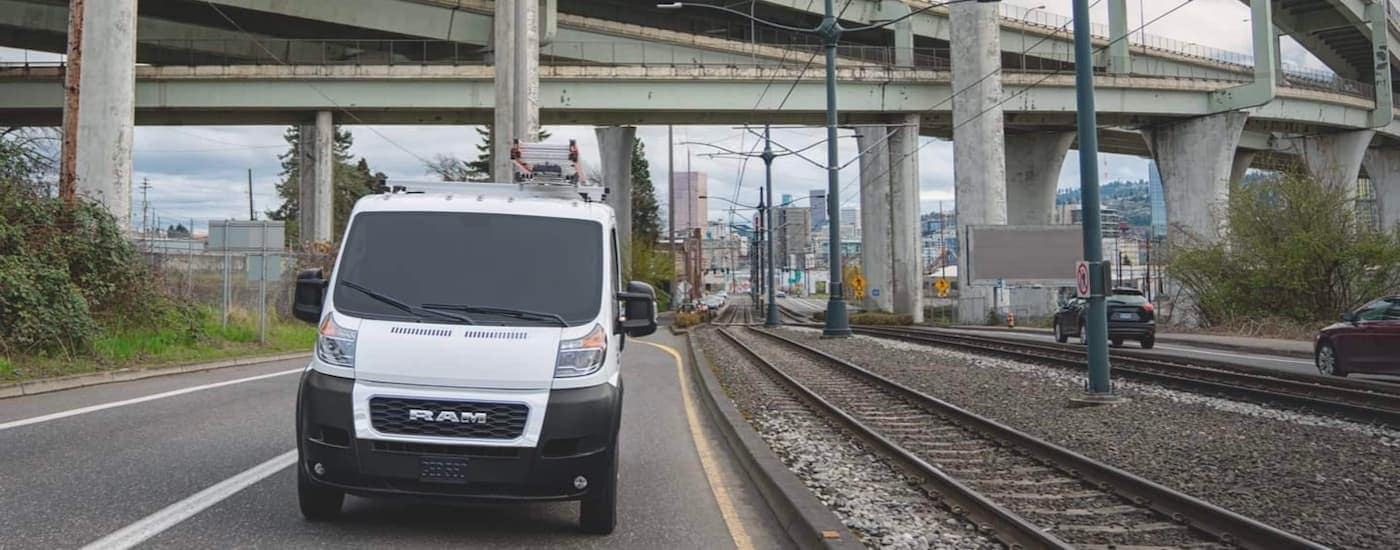 A popular Ram commerical vehicle, a white 2021 Ram Promaster, is shown driving through an overpass next to train tracks.