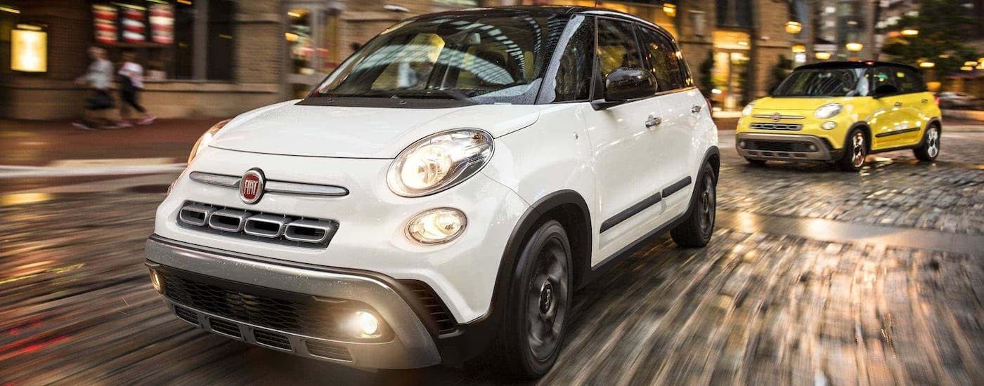 A white and a yellow 2020 Fiat 500L are driving on a wet cobblestone city street.