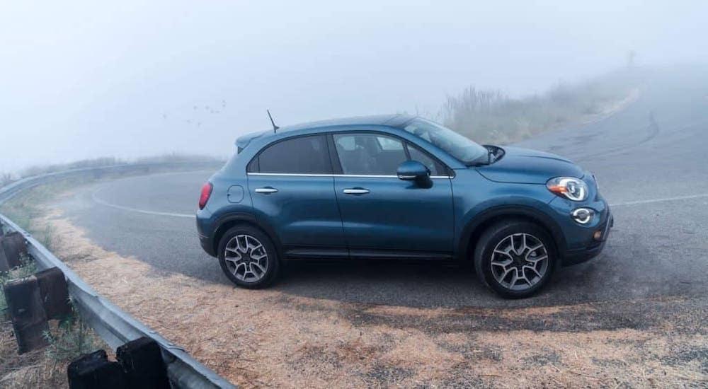 A blue 2020 Fiat 500x is driving around a misty corner.