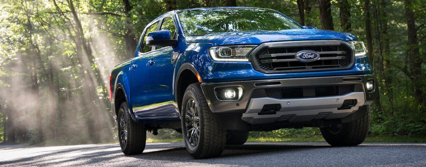 A blue 2020 Ford Ranger is driving on a woodland road after leaving a used pickup dealership.