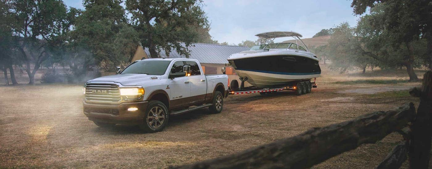 A white 2020 Ram 2500 is towing a boat in front of a farm after leaving a used pickup dealer.