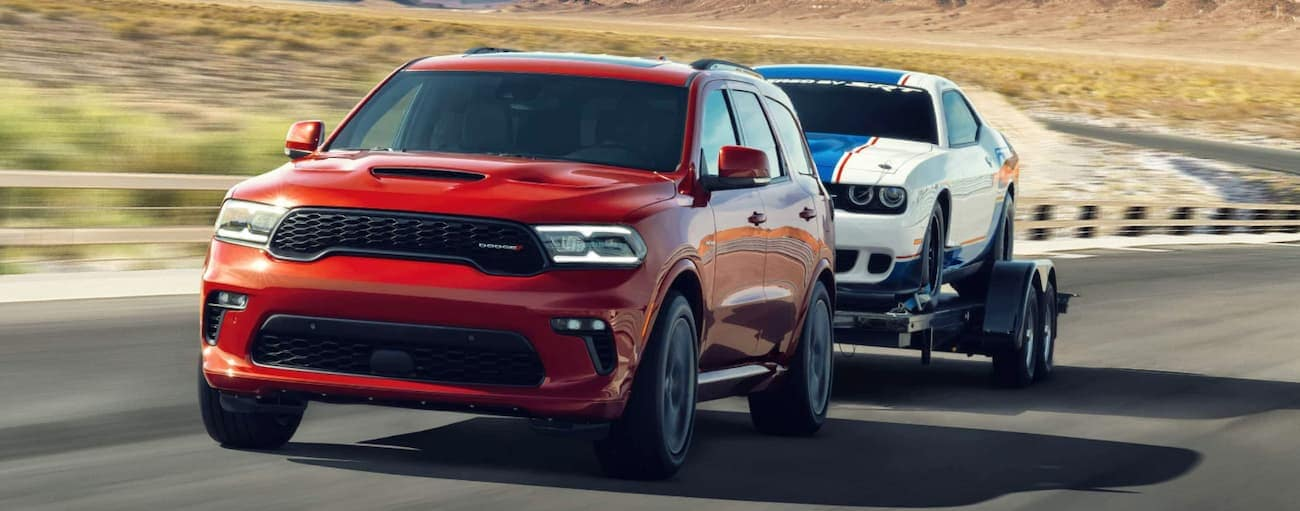 A red 2021 Dodge Durango is towing a white car on a trailer on a rural road.