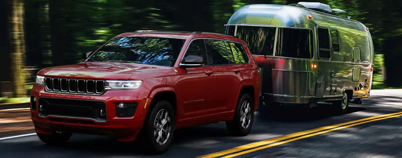 A red 2021 Jeep Grand Cherokee L is towing an Airstream on a tree-lined road.