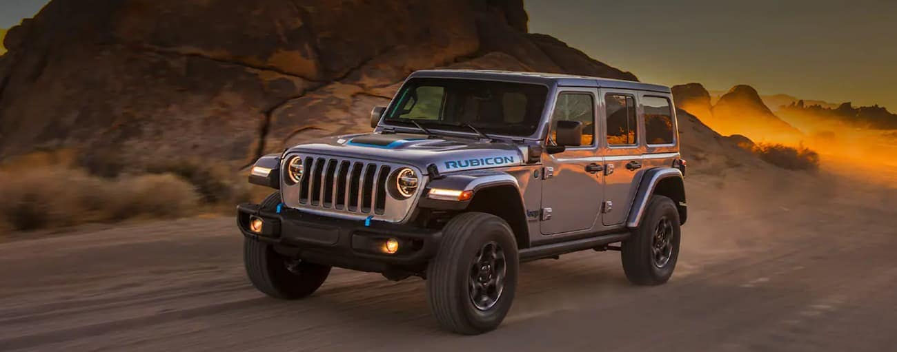 A grey 2021 Jeep Wrangler 4xe is driving on a dirt road in the desert.