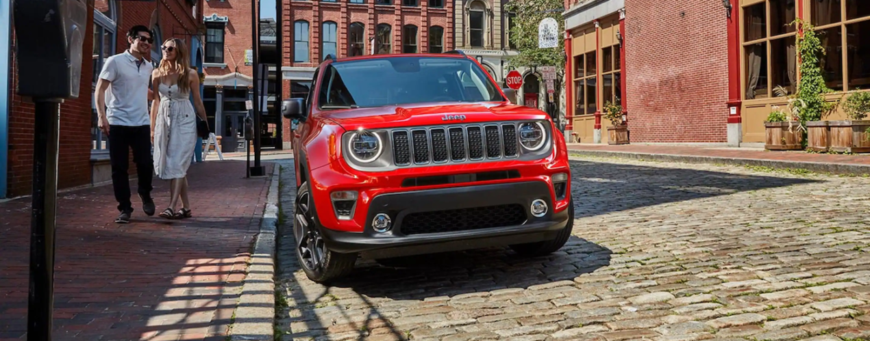 A red 2021 Jeep Renegade is shown from the front parked on a brick street.