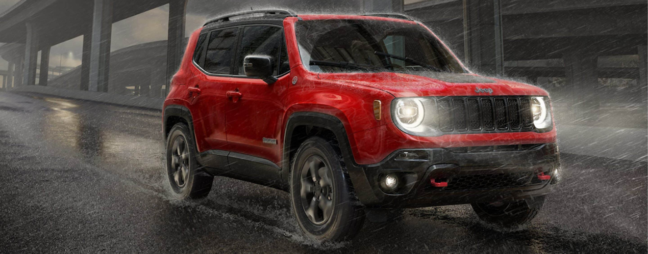 A red 2021 Jeep Renegade Trailhawk is shown from the side driving through the rain in the dark.