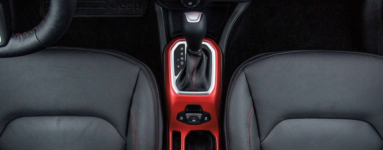 A close up shows the red shifter surround and black interior from a high angle in a 2021 Jeep Renegade Trailhawk.