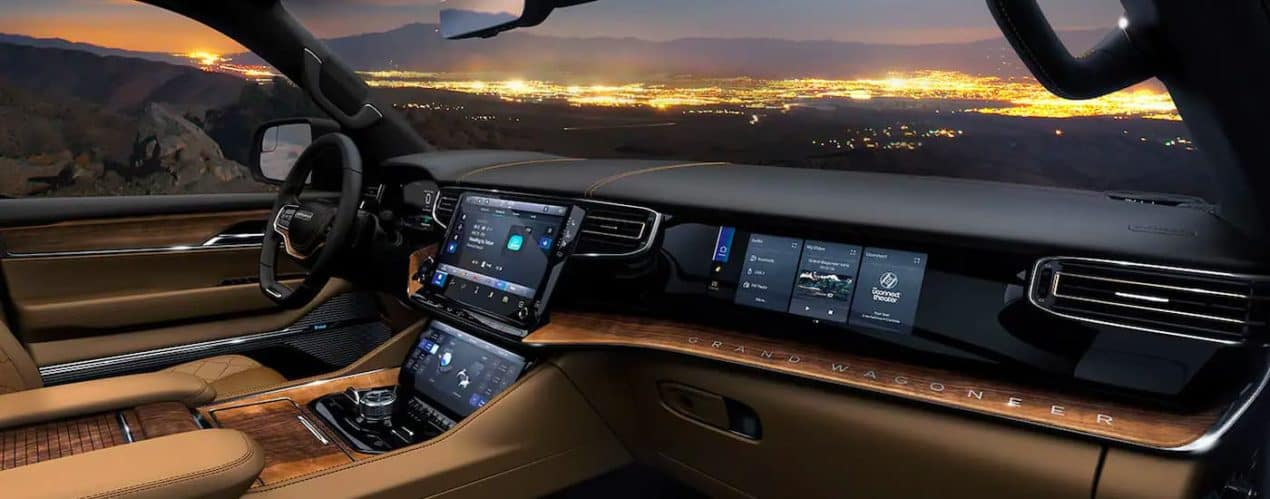 The black, tan, and woodgrain interior is shown in a 2022 Grand Wagoneer while overlooking city lights.