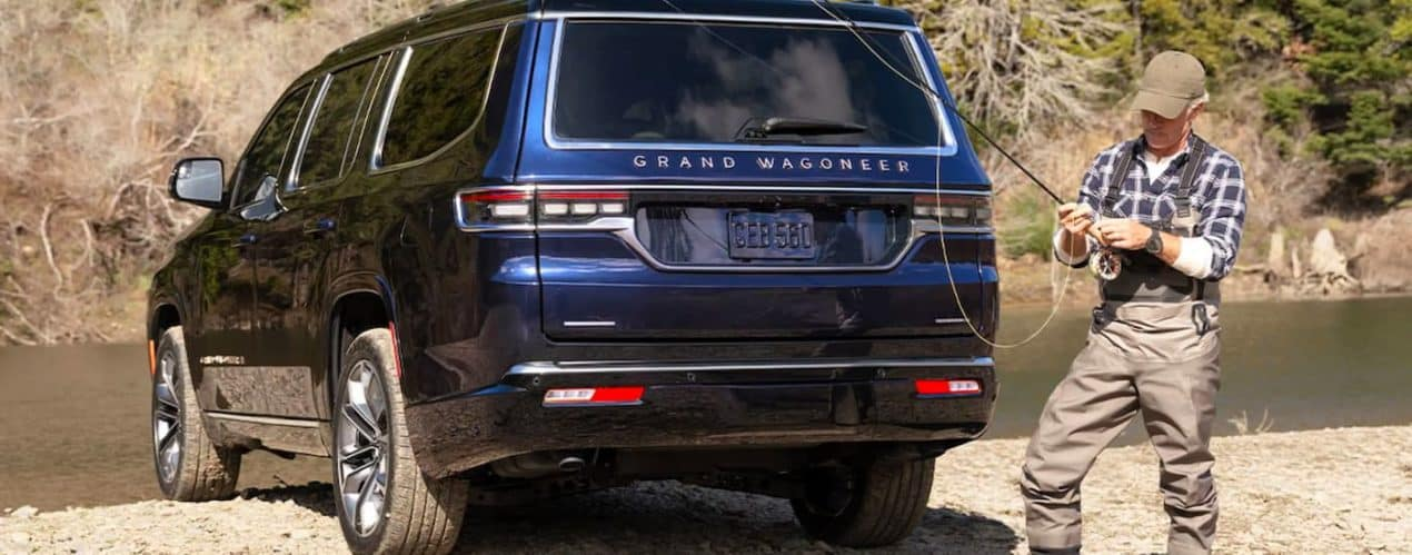 A dark blue 2022 Grand Wagoneer is shown from the rear next to a man fly fishing.